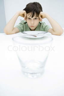 ©Odilon Dimier/AltoPress/Maxppp ; Boy sulking at kitchen table, leaning on elbows, empty glass in foreground
