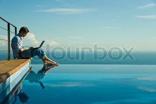 ©Sigrid Olsson/AltoPress/Maxppp ; Man sitting beside infinity pool, using laptop computer