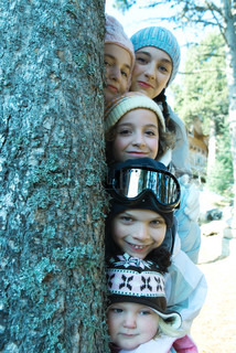 ©Laurence Mouton/AltoPress/Maxppp ; Kids and teens peeking from behind tree in ski clothes, portrait