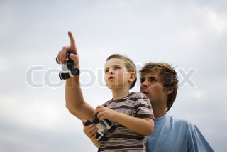 ©Ale Ventura/AltoPress/Maxppp ; Father and son looking up at sky, holding binoculars