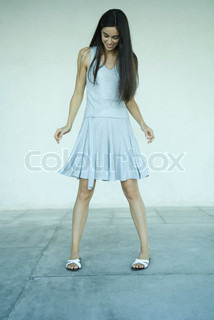 ©Eric Audras/AltoPress/Maxppp ; Young woman standing, wearing dress, looking down, full length portrait