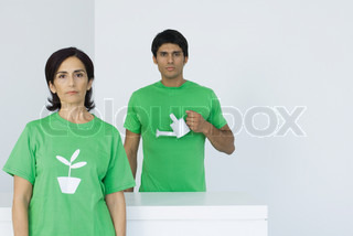 ©Michèle Constantini/AltoPress/Maxppp ; Woman wearing tee-shirt with plant graphic, man holding watering can in background