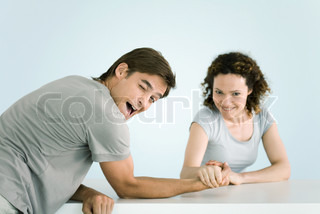 ©Ale Ventura/AltoPress/Maxppp ; Couple arm wrestling, both looking at camera, man winking as he lets woman win