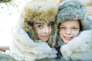 ©Laurence Mouton/AltoPress/Maxppp ; Brother and sister smiling at camera, cheek to cheek, both wearing fur caps, portrait