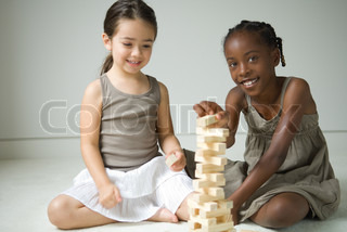 ©Eric Audras/AltoPress/Maxppp ; Two girls sitting on floor playing with blocks, one smiling at camera
