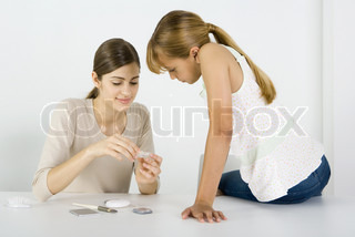 ©Laurence Mouton/AltoPress/Maxppp ; Young woman and preteen sister looking at cosmetics together, smiling