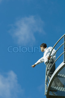 ©Eric Audras/AltoPress/Maxppp ; Businessman standing on metal balcony, pointing to distance, low angle view, blue sky in background