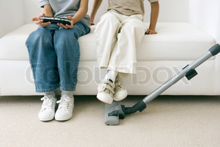 ©Sigrid Olsson/AltoPress/Maxppp ; Two children sitting on sofa as parent vacuums, one playing handheld video game, cropped view