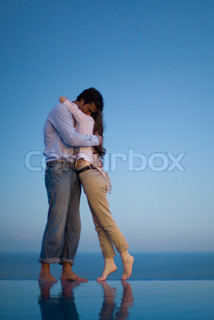 ©Sigrid Olsson/AltoPress/Maxppp ; Couple embracing on edge of infinity pool at dusk