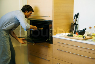 ©Eric Audras/AltoPress/Maxppp ; Man putting pan into oven