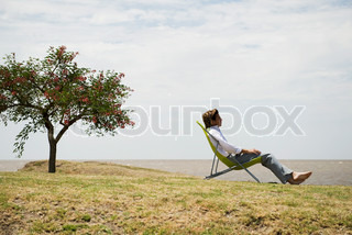 ©Eric Audras/AltoPress/Maxppp ; Man relaxing in lounge chair outdoors contemplating sea shore view