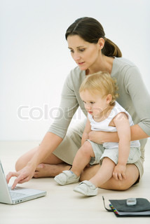 ©Alix Minde/AltoPress/Maxppp ; Professional woman sitting on the ground, using laptop, holding toddler on lap