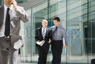 ©Sigrid Olsson/AltoPress/Maxppp ; Two businessmen walking together, discussing, building in background