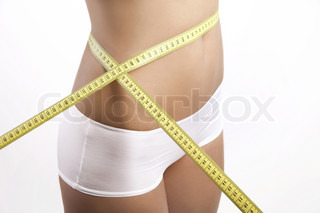 ©Jana Hernette/AltoPress/Maxppp ; Young woman measuring waist with measuring tape, cropped