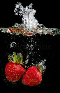 Fresh strawberries are dropped into water on black background