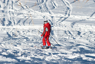 Woman in red and ski traces on snow