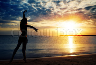 Dancing lady outdoors during sunset at the sea
