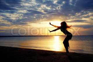 Active woman dancing at the beach during sunset