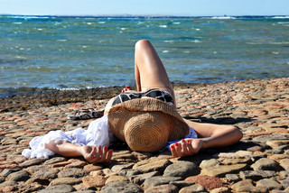 caucasian woman in straw hat lying on the stone beach in Egypt