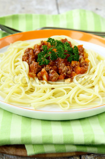 Bolonnez spaghetti on a plate with a fork and spoon