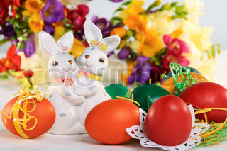 Easter bunnies and colored eggs on the background of spring colors.