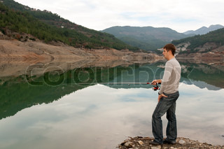man with a fishing rod on the bank of a mountain lake