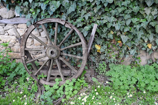 Medieval wooden wheel against the background of the stone wall and vegetation