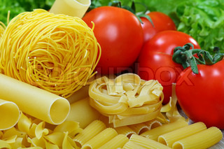 Different varieties of pasta, ripe tomatoes and greens.