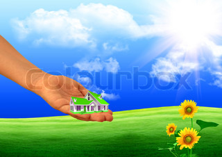 Hand of the child holding model of the house