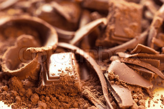 Chocolate background. Bars and strips of chocolate with cocoa powder. Shallow depth of field