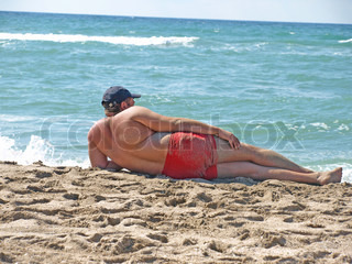 Man lying on the sand at the beach and looks into the distance.