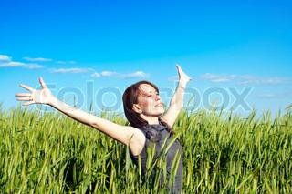 ung kvinde med hænderne hævet op i kornmark