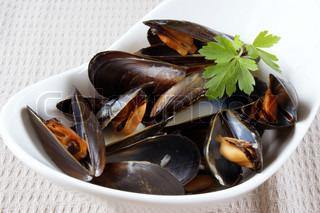Muslinger kogt med hvidvin sauce i en hvid skål