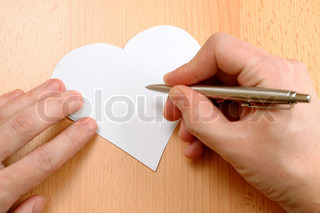 Hand with pen writing on Valentine's Day card in form of heart
