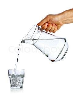 Hand hælde vand fra glas kande til glas mod hvid baggrund