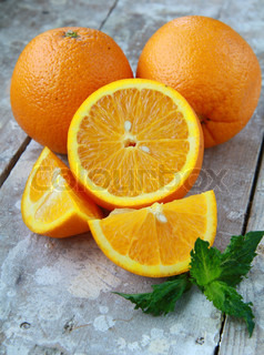 cut into slices and whole oranges with mint leaf