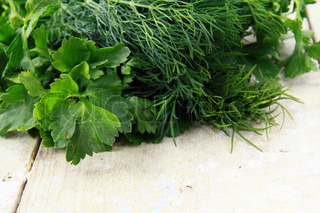 Fresh food dill and parsley on a wooden table