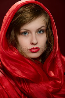 Attractiv young girl fashion portrait clouse up with magnetic red head covering in studio