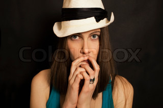 Studio shoulder portrait of young blue-eyed girl in white hat on black background