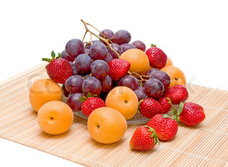 still life of fruit. fresh apricots, grapes and strawberries on a white background