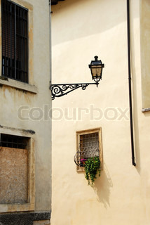 street lamp on building corner and small window, architecture details of Verona, Italy