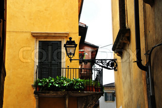 street lamp on building wall and balcony on yellow building facade, architecture details of Verona, Italy