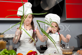 two little girls in clothes cooks in the kitchen at the table with raw food, with bunches of green onions in the hands of