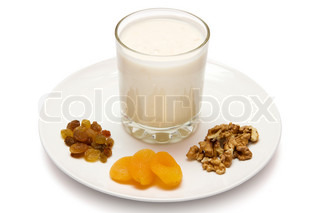 glass of  yogurt served with nuts, raisins and dried apricots