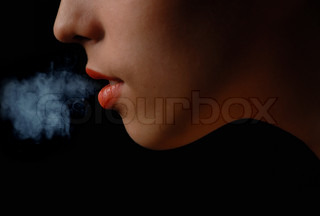 Half-face of the smoking woman on a black background