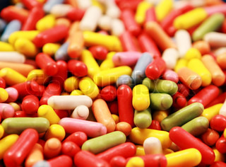 many candy with different colors with shape of pills