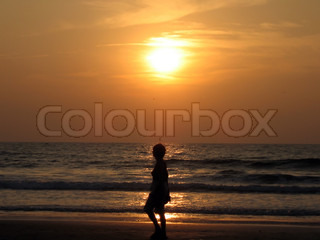 Woman silhouette at the sunset beach