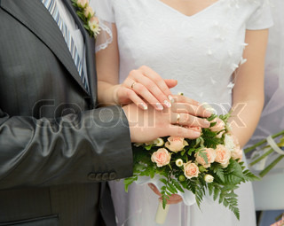 Hands of a newly-married couple. Tenderness of the groom and the bride above wedding a bouquet