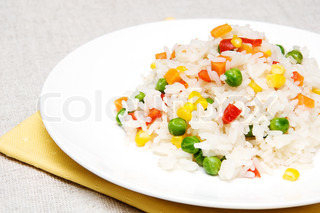 boiled rice with green peas, corn, sweet peppers and carrots on a white plate
