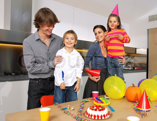 Happy family having fun while eating birthday cake in the kitchen